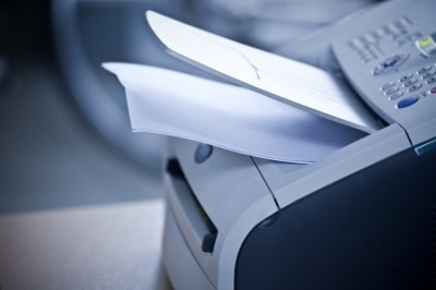 Laserdrucker mit einem Stapel ausgedruckter Rechnungen