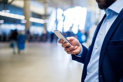Geschäftsmann mit Smartphone am Bahnhof